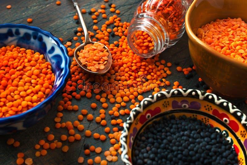 Черная и красная чечевица в керамических блюдах на темном backgroun стоковые фото