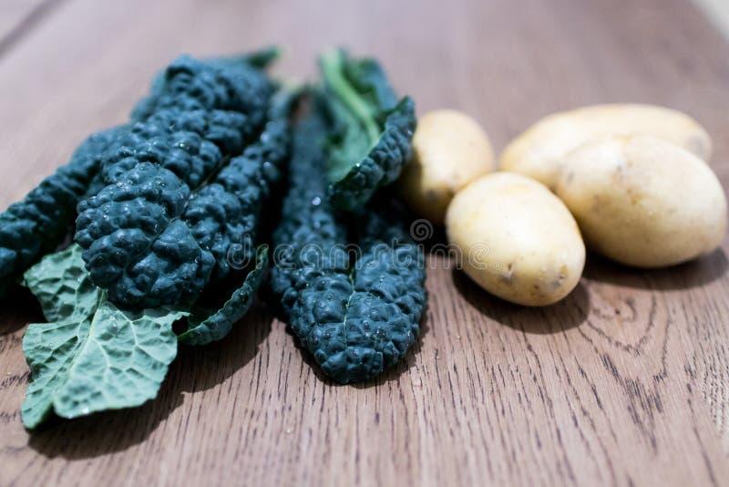Черная капуста выходит с картошками на деревянный стол Органическое стоковые изображения