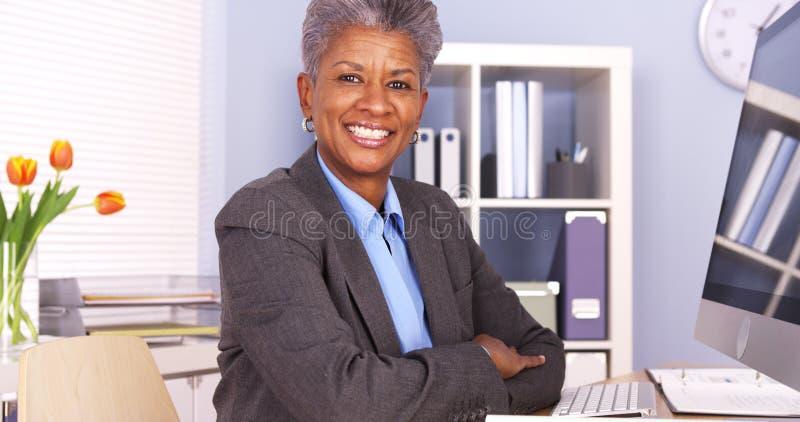 Черная коммерсантка сидя на усмехаться стола стоковая фотография