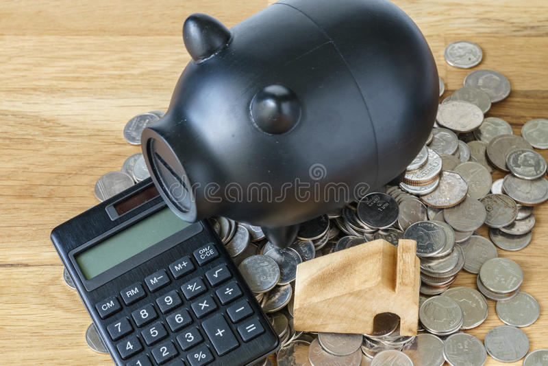 Черная копилка с калькулятором и монетки как сбережения или financia стоковые фото