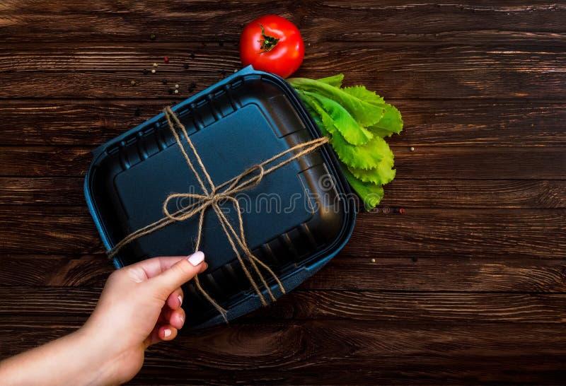 Черная коробка для завтрака связанная со жгутиками Еда на темной коричневой деревянной поверхности Закрытая коробка для еды, тома стоковое изображение
