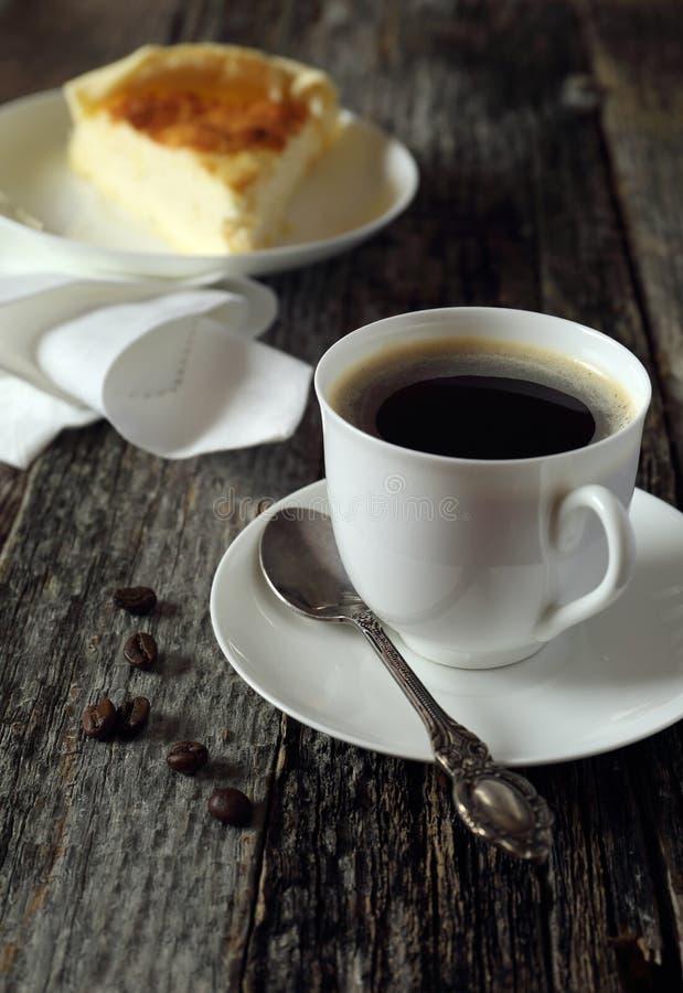 Черная кофейная чашка и чизкейк стоковое изображение rf