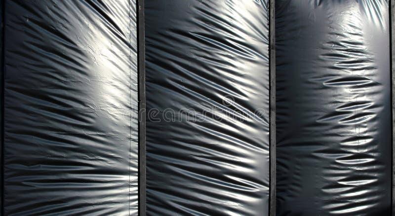 Черная опухнутая фольга полиэтилена как предпосылка стоковые фото