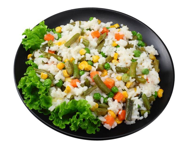 Черная плита с белым рисом, зелеными горохами, законсервированными стерженями мозоли, отрезать зеленые фасоли изолированные на бе стоковое изображение