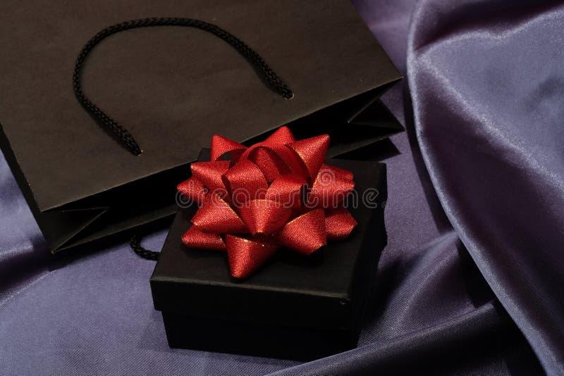 Черная подарочная коробка с черной хозяйственной сумкой на темной ткани стоковые изображения