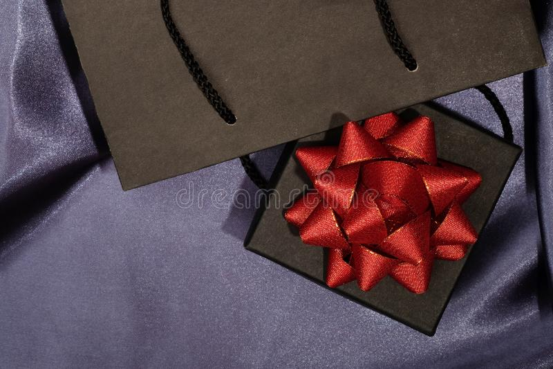 Черная подарочная коробка с черной хозяйственной сумкой на темной ткани стоковые фото