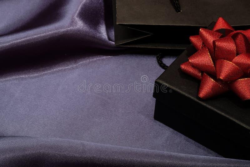 Черная подарочная коробка с черной хозяйственной сумкой на темной ткани стоковые изображения rf