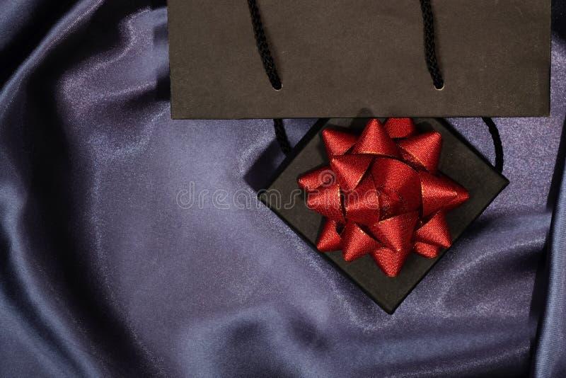 Черная подарочная коробка с черной хозяйственной сумкой на темной ткани стоковое фото