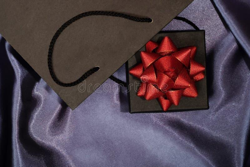 Черная подарочная коробка с черной хозяйственной сумкой на темной ткани стоковая фотография rf