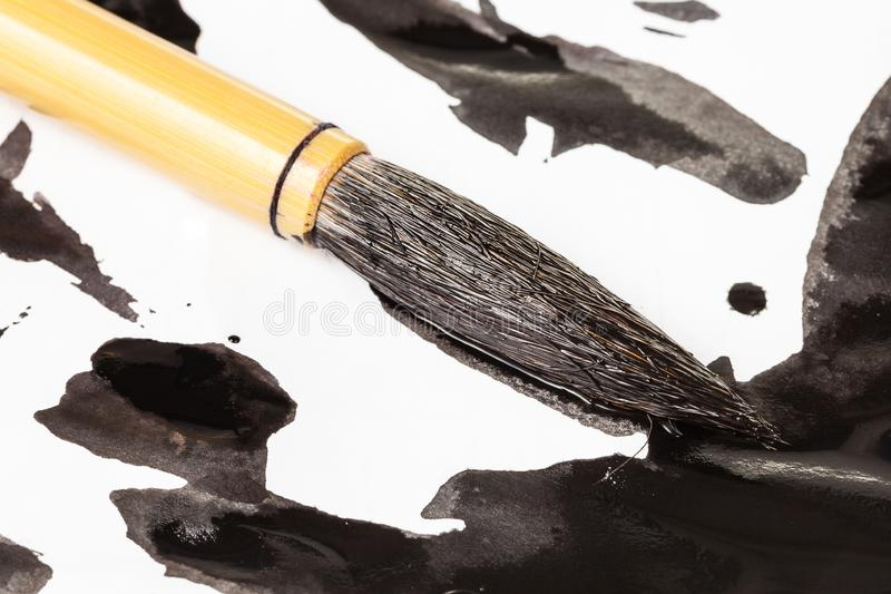 Черная подсказка paintbrush над пятнами чернил близко вверх стоковое изображение