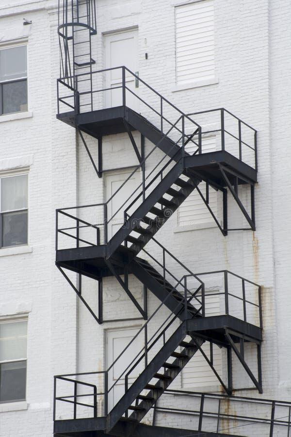 Черная пожарная лестница, белое здание стоковые фотографии rf