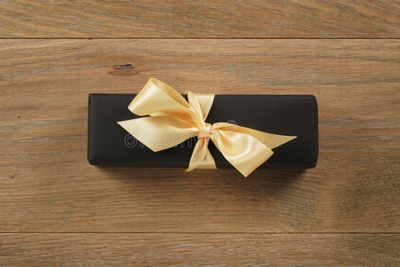 Черная подарочная коробка прямоугольника с смычком ленты цвета шампанского на деревянной таблице дуба сверху стоковая фотография rf