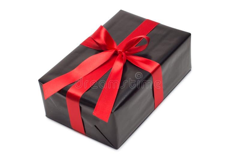 Черная подарочная коробка с красными лентой и смычком сатинировки стоковое фото rf