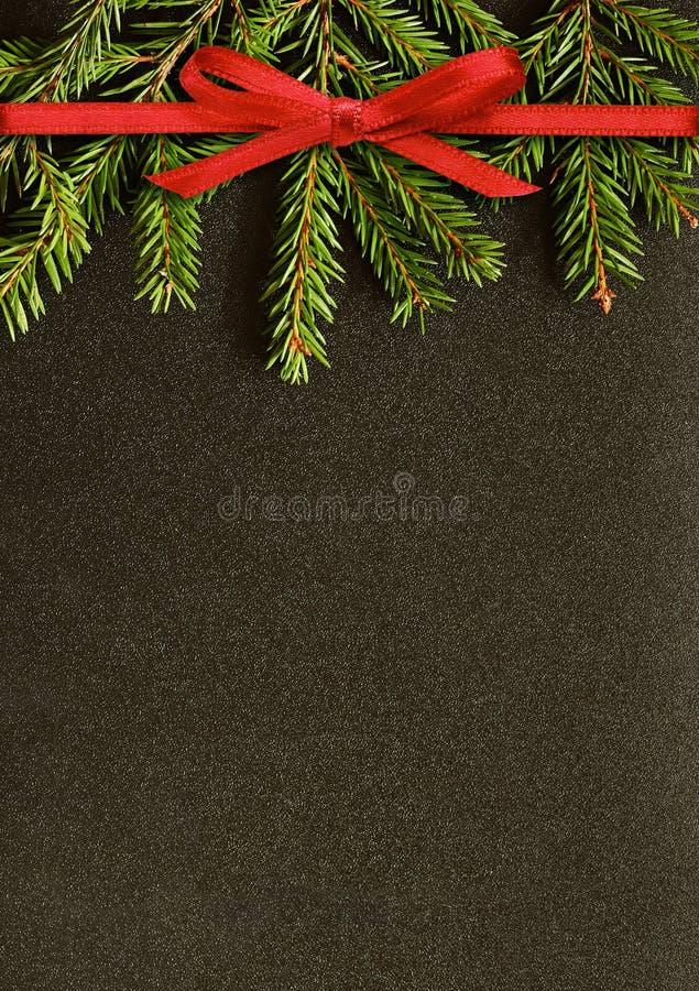 Черная предпосылка рождества с хворостинами ели и красной лентой bo стоковые фотографии rf