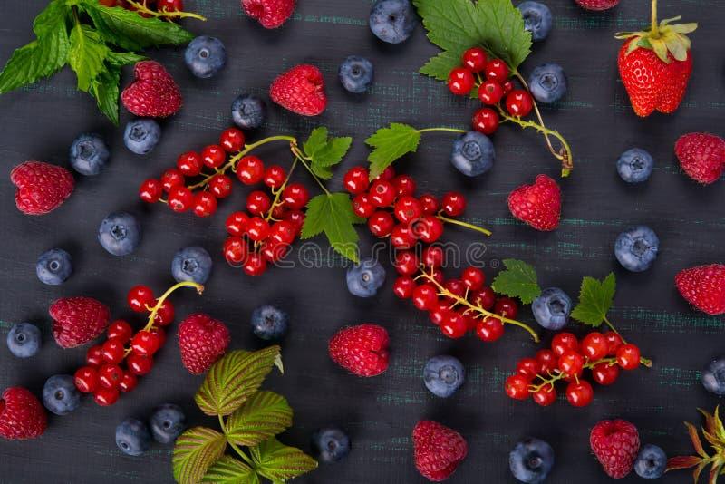 Черная предпосылка с ягодами красной смородины на поверхности смешала с голубиками стоковое фото rf
