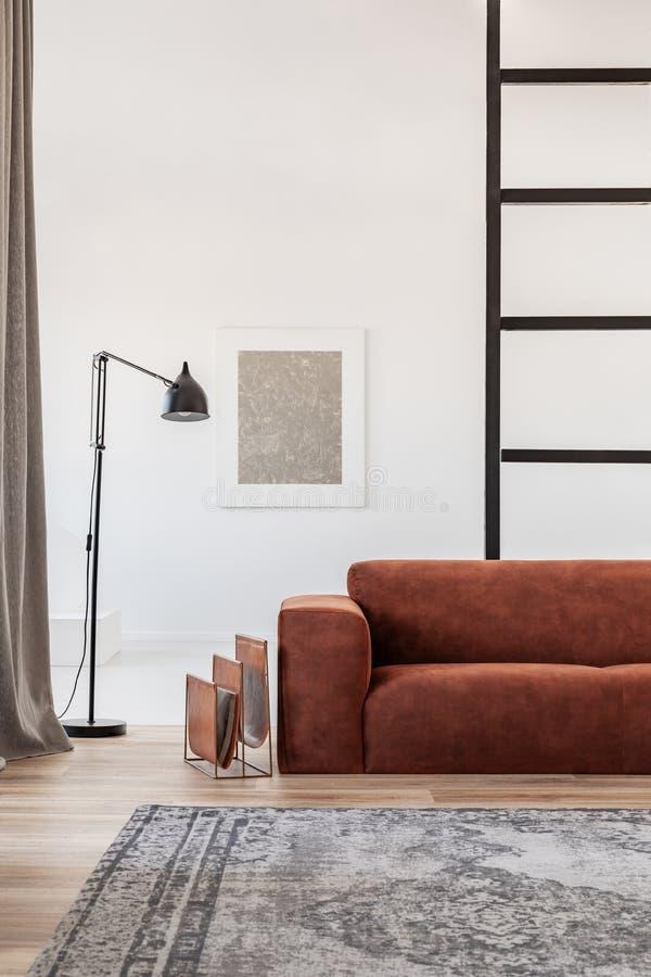 Черная промышленная лампа рядом с модной скандинавской софой в ярком интерьере живущей комнаты стоковая фотография