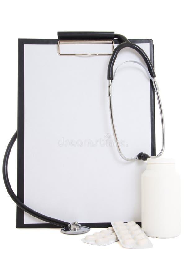Черная пластичная доска сзажимом для бумаги с листом, пилюльками и stetho чистого листа бумаги стоковое изображение rf