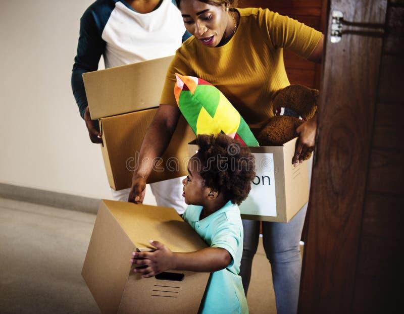 Черная семья двигая внутри к новому дому стоковая фотография