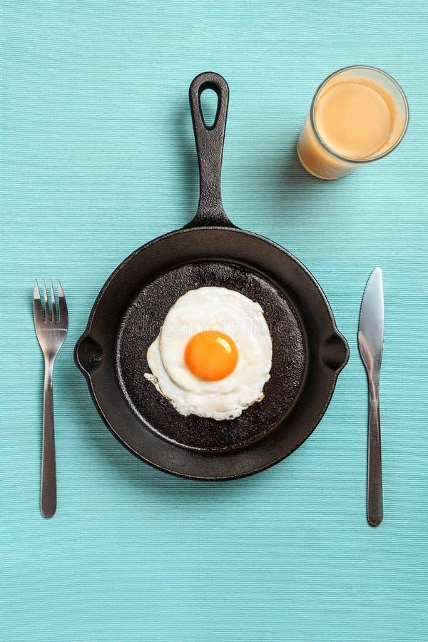 Черная сковорода с взбитыми яйцами, вилка, нож, стекло апельсинового сока на скатерти бирюзы стоковые изображения