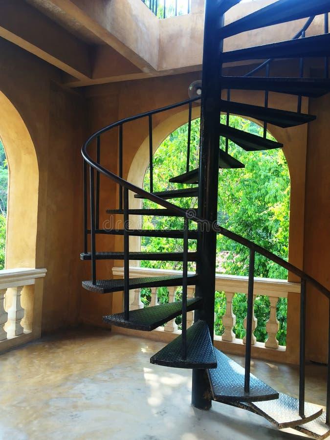 Черная спиральная стальная лестница внутри здания стоковое изображение