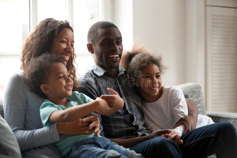 Черная счастливая семья совместно сидя на кресле дома стоковые изображения
