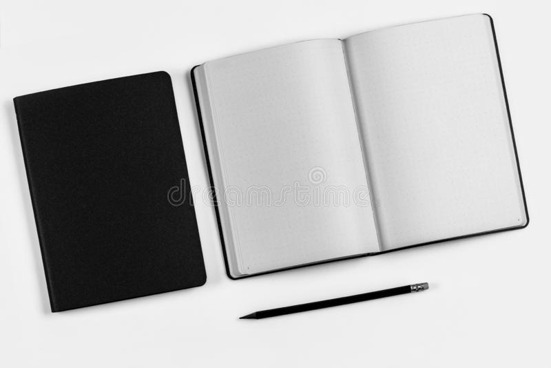 Черная тетрадь 2 с черным карандашем на белой предпосылке стоковое фото rf