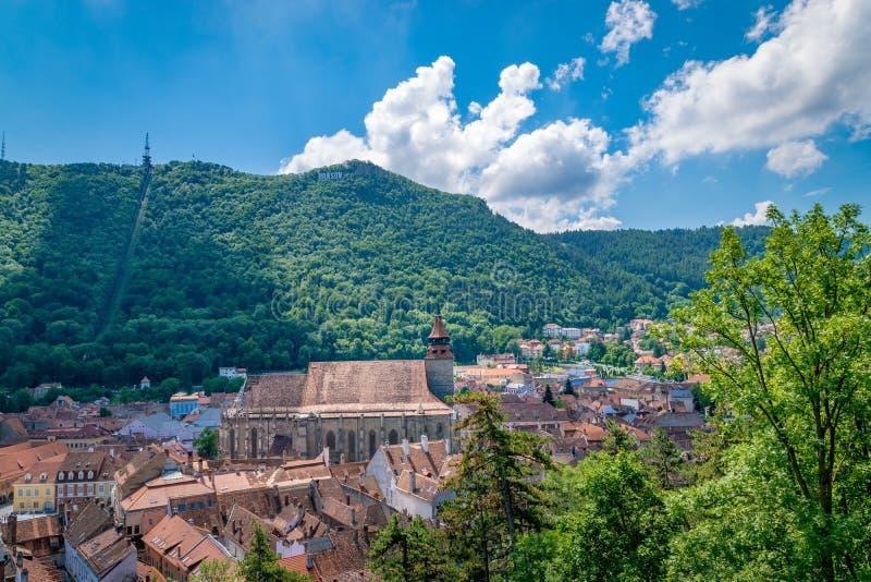 Черная церковь с знаком Brasov и горой Тампа на заднем плане стоковое изображение
