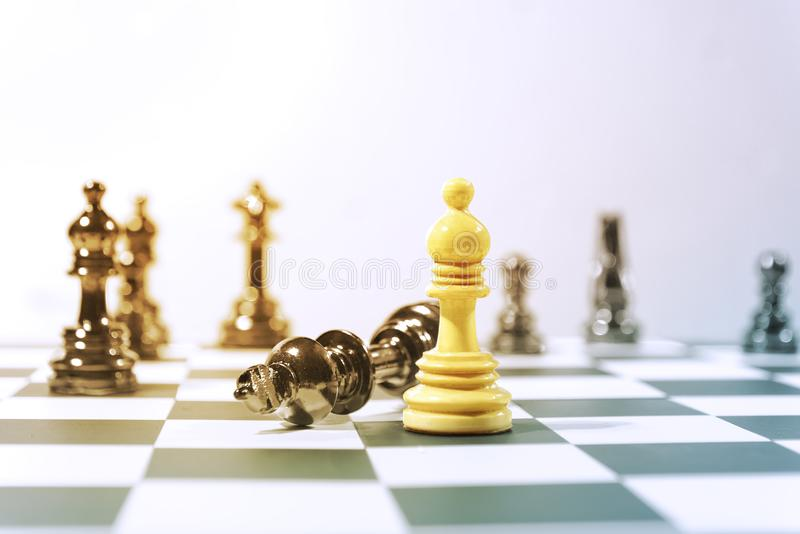 Черная шахматная фигура короля нанесла поражение коричневой шахматной фигурой епископа стоковые фотографии rf
