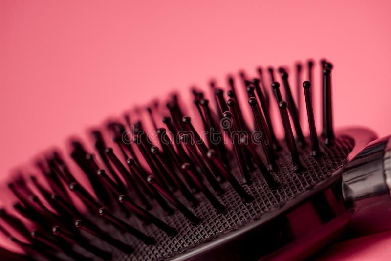 Черная щетка для волос на розовой предпосылке стоковые фотографии rf