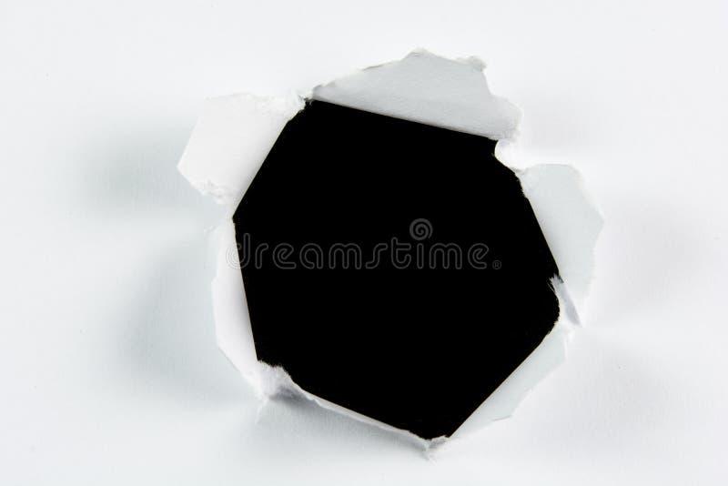 Черная дыра сорванная прорывом большая в белой бумаге стоковые фото