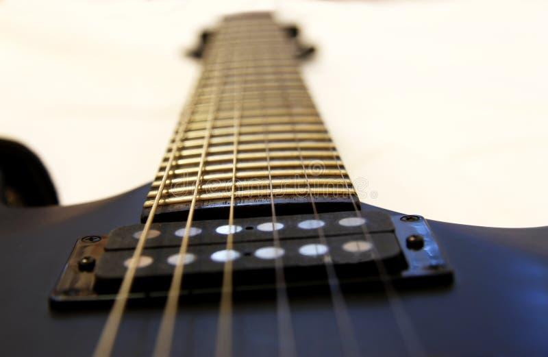 Черная электрическая гитара изолированная на белом backgriund стоковые изображения