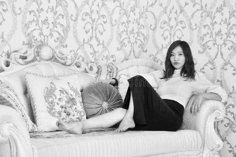 Черное белое фото молодой азиатской сексуальной модели при длинные ноги лежа на софе стоковое фото rf