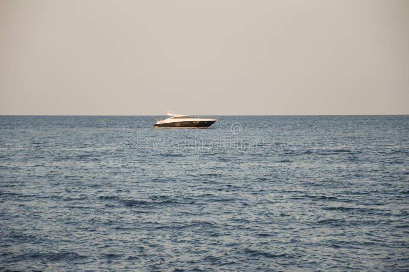 черное море Вода без волн и меньшей шлюпки далеко затишье Главным образом пасмурная погода Голубой и серый цвет Перед дождем стоковое изображение