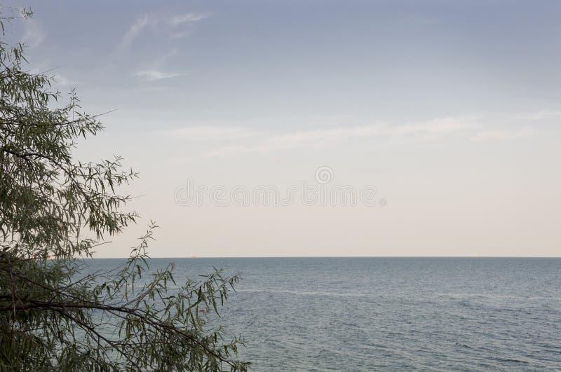 черное море Вода без волн и меньшей шлюпки далеко затишье Главным образом пасмурная погода Голубой и серый цвет Перед дождем стоковые фото