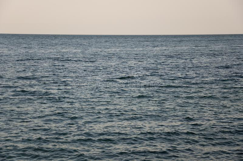 черное море Вода без волн и меньшей шлюпки далеко затишье Главным образом пасмурная погода Голубой и серый цвет Перед дождем стоковое фото rf
