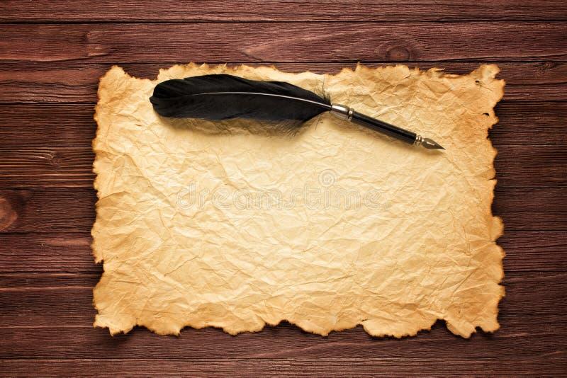 Черное перо и старая бумага на предпосылке коричневой таблицы стоковое фото rf