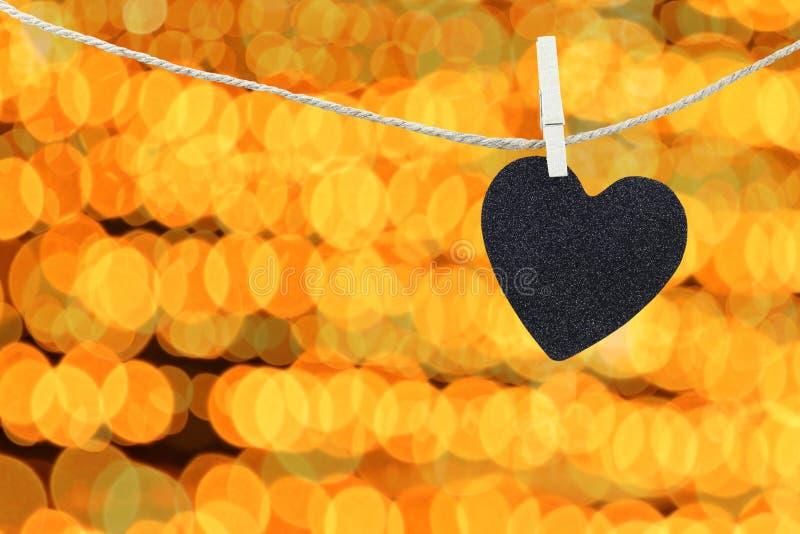 Черное сердце повиснуло на пеньковой веревке на абстрактном красочном backgro bokeh стоковые изображения