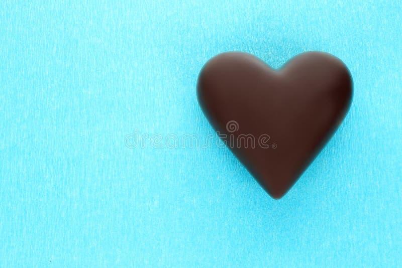 Черное сердце шоколада на голубой предпосылке стоковое фото