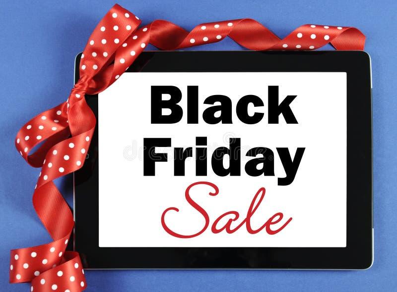 Черное сообщение продажи пятницы на черном приборе таблетки компьютера с красной лентой стоковая фотография rf