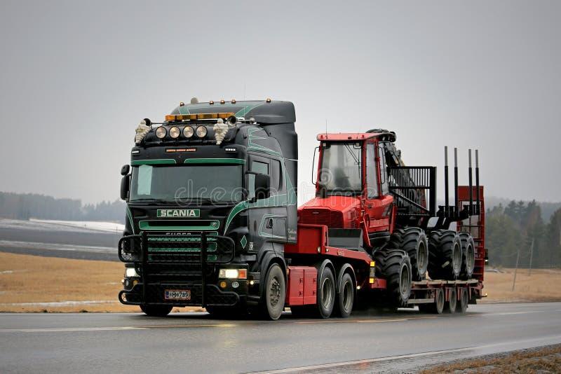 Черное супер Scania транспортирует машинное оборудование лесохозяйства вдоль дороги стоковое фото