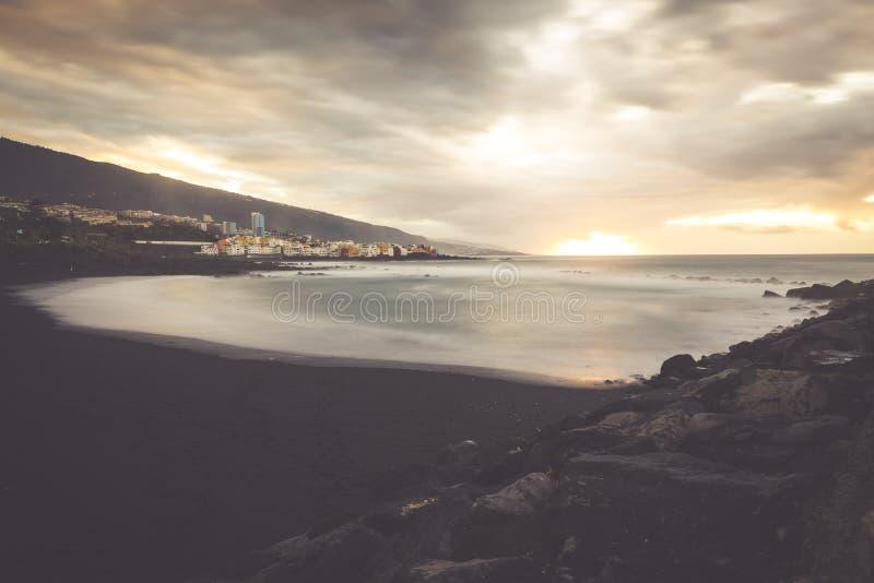 Черное Pebble Beach в Puerto de Ла Cruz заходом солнца, Тенерифе стоковые фотографии rf