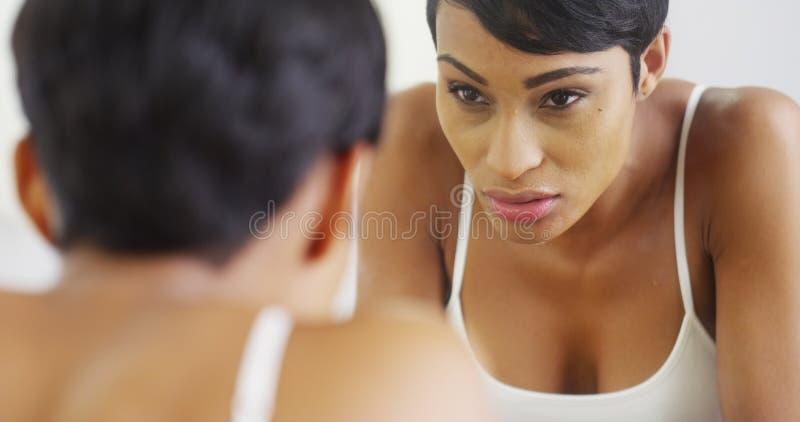 Чернокожая женщина брызгая сторону с водой и смотря в зеркале стоковое изображение rf
