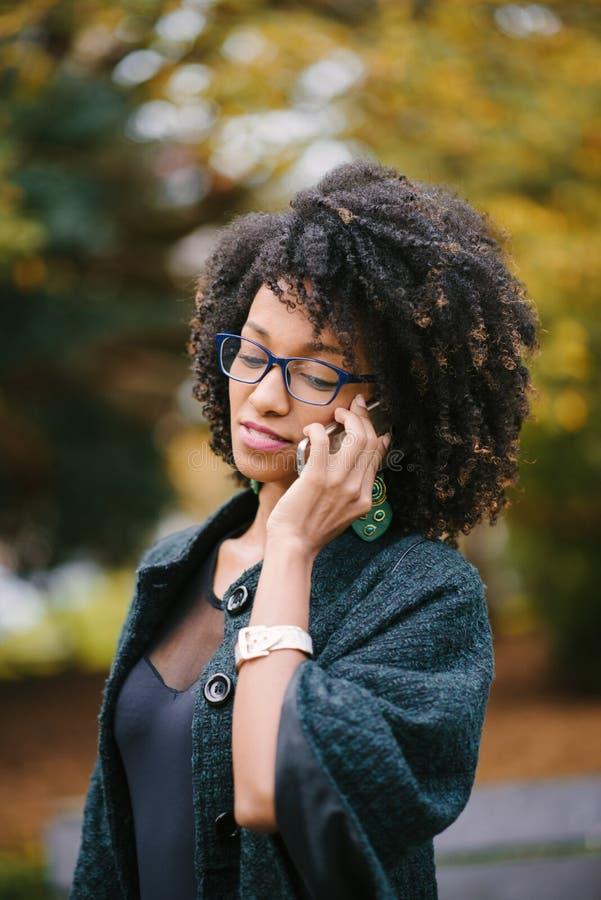 Чернокожая женщина во время звонка мобильного телефона в осени стоковое изображение rf