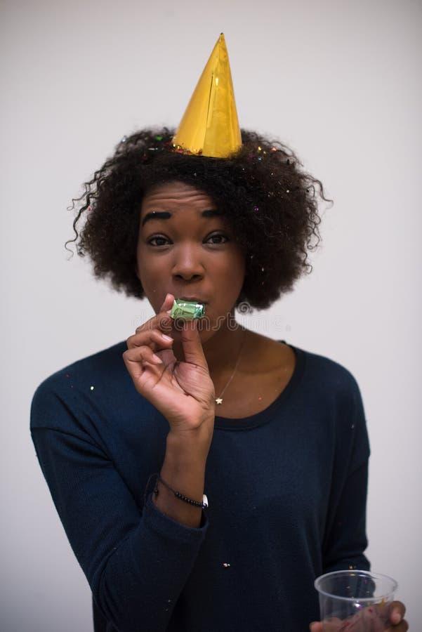Чернокожая женщина в шляпе партии дуя в свистке стоковая фотография rf