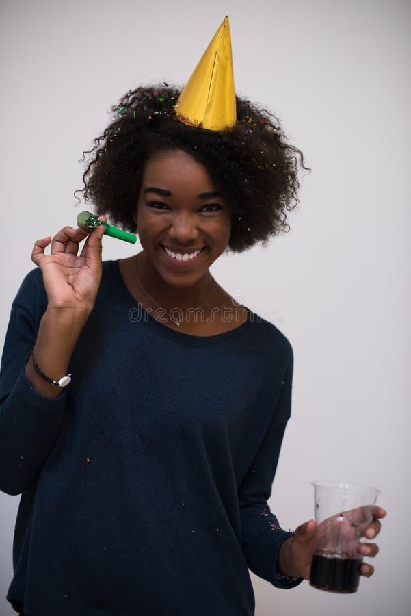 Чернокожая женщина в шляпе партии дуя в свистке стоковое фото