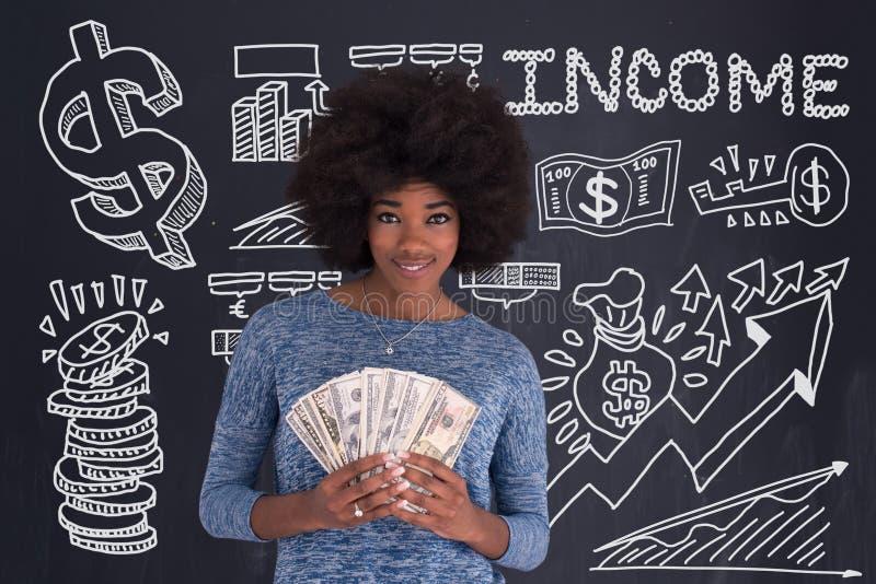 Чернокожая женщина держа деньги на серой предпосылке стоковые фотографии rf