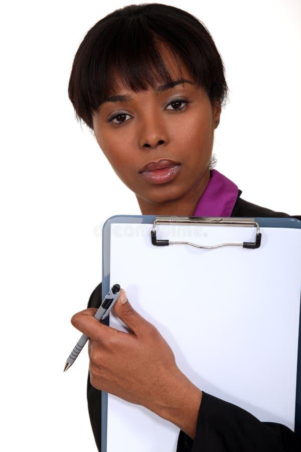 Чернокожая женщина держа доску сзажимом для бумаги. стоковые изображения rf