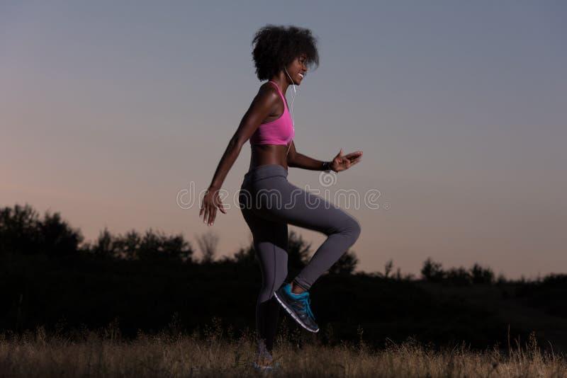 Чернокожая женщина делает протягивающ ослаблять и подогрев тренировки стоковые изображения rf