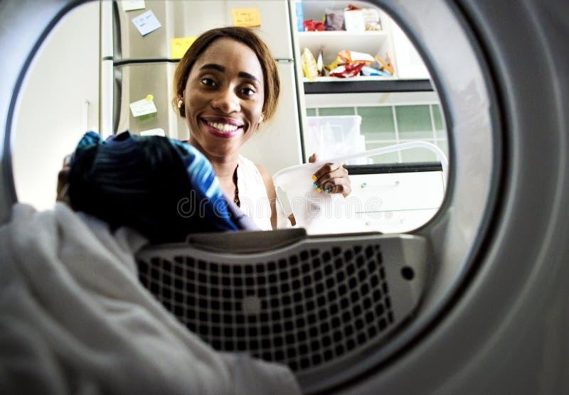 Чернокожая женщина используя стиральную машину делая прачечную стоковое фото