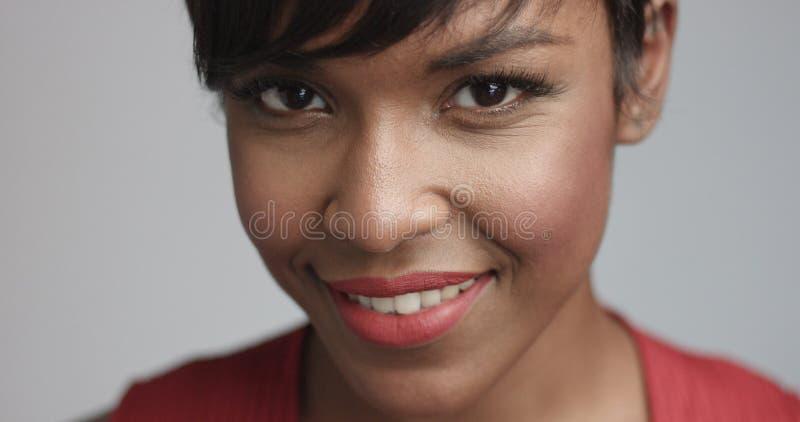 Чернокожая женщина смешанной гонки в красном платье танцуя и представляя к камере стоковая фотография